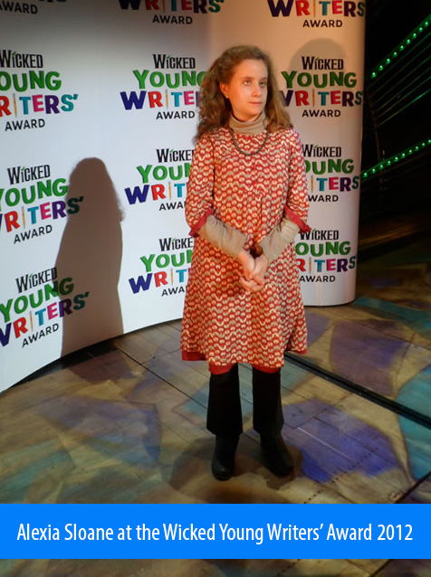 Alexia Sloane at the Wicked Young Writers' Award 2012. Image. Alexia stands on the carpet in front of a backdrop with the competition's logo repeated in a pattern.