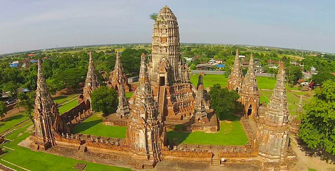 Image: Aerial view of Ayutthaya Historical Park with a central temple surrounded nu a square wall with 8 prangs or towers at each corner and in the middle of each wall.