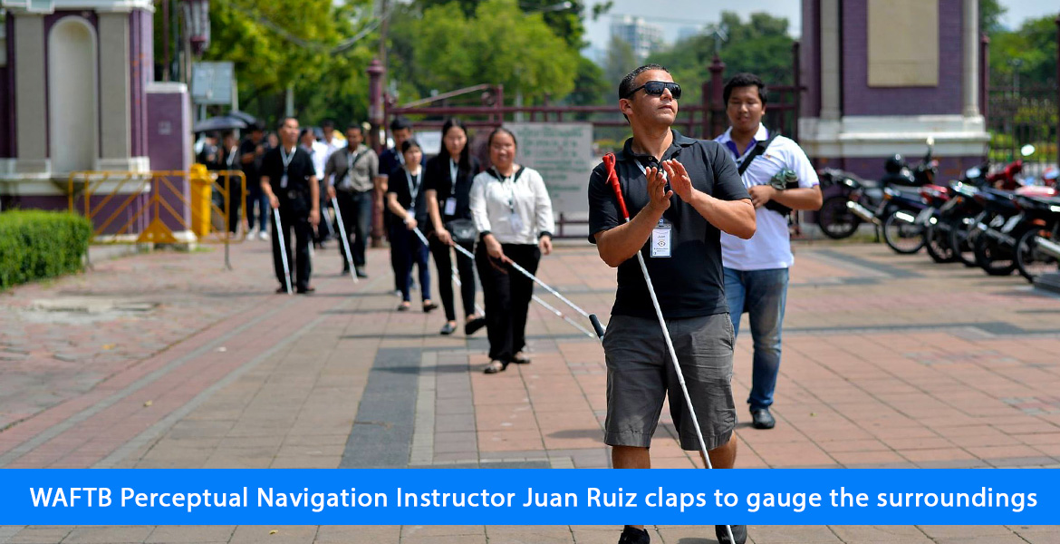 WAFTB Perceptual Navigation Instructor Juan Ruiz claps to gauge the surroundings. Image. Juan Ruiz leads blind students into an open square in Bangkok as they navigate with their full-length canes.