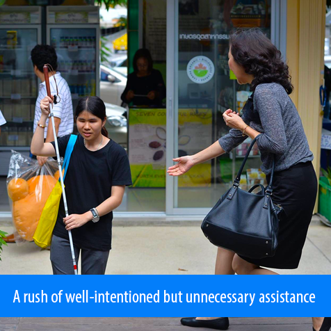 A rush of well-intentioned but unnecessary assistance. Image shows a woman rushing to help one of the blind female students as she approaches some stairs.