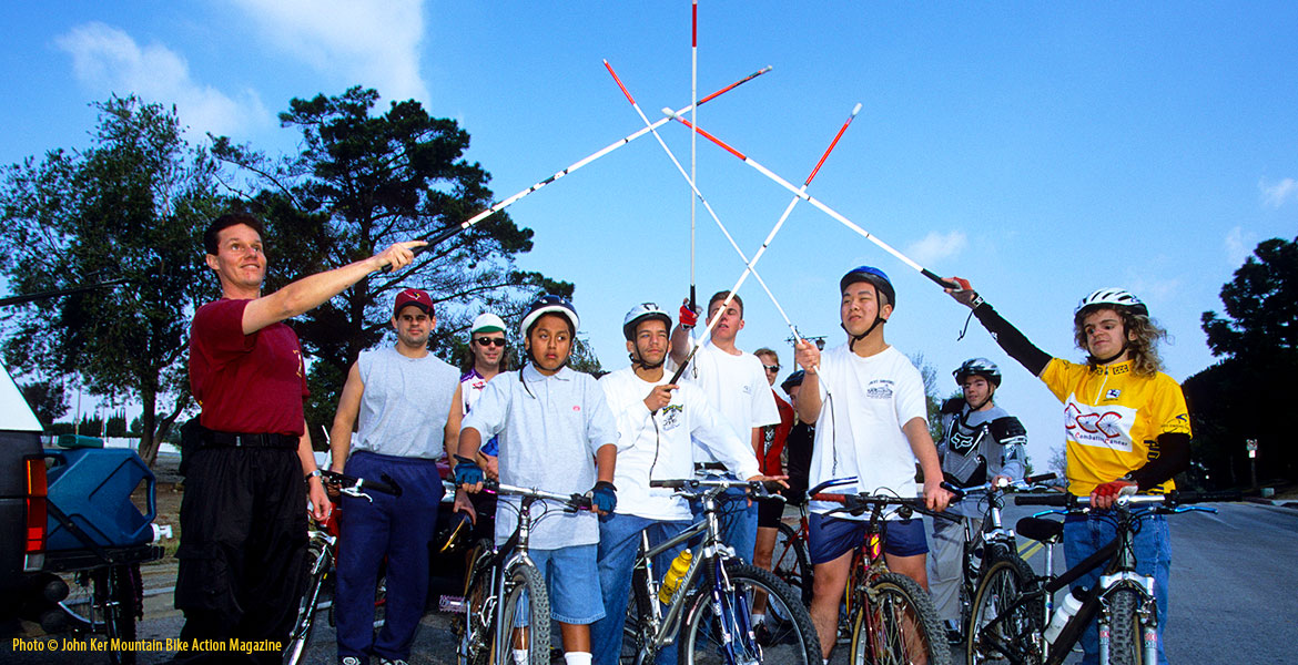 "Photo: Lead Visioneer Daniel Kish stands with blind students sitting on, or standing beside, their mountain bikes raising their canes in the air in an ""All for one, one for all"" salute. Photo by John Ker for an article in the May 2001 edition of Mountain Bike Action Magazine."