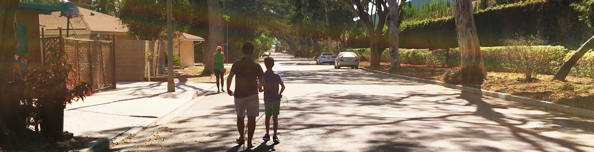 Image: Lead Visioneer Daniel Kish instructs Junior Visioneer Nava along a tree-lined street.