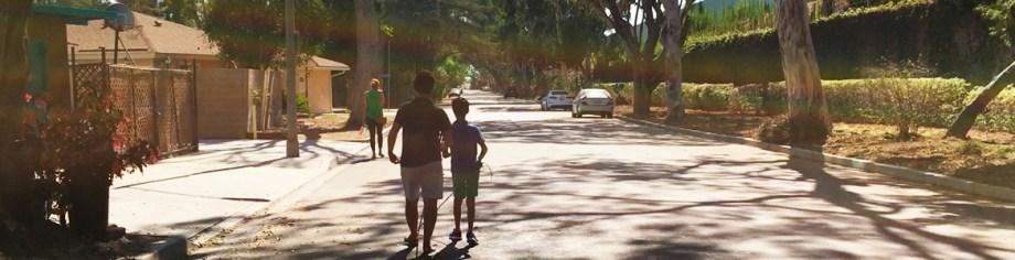 Image: Lead Visioneer Daniel Kish instructs Junior Visioneer Nava along a tree-lined street.