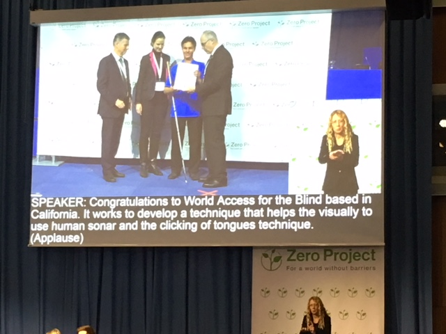 Image: Photo of the large projection screen above the speaker's area at the Zero Project 2018 Conference at the United Nations in Vienna, Austria. Daniel Kish is being presented with the Innovative Practice Award as a person signing for Deaf attendees appears in an adjacent video frame. Text on the screen reads: Speaker: Congratulations to World Access For THe Blind based in California. It works to develop a technique that helps the visually-impaired to use human sonar and the clicking of tongues technique. (Applause).