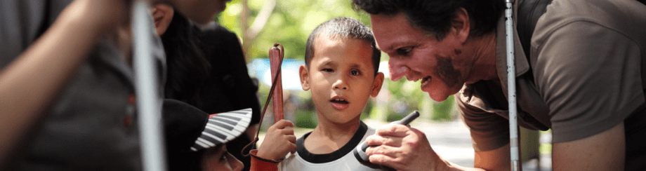 Photo of Daniel Kish teaching FLashSonar to a young Thai Boy.