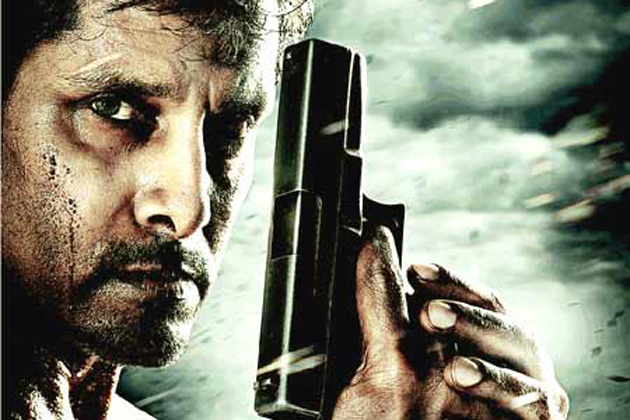 Promotional photo from the movie Thaandavam shows lead actor Vikram holding a revolver.