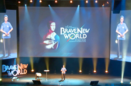 "Daniel Kish stands center stage during his Keynote Speech at the Aspire Conference in Krakow, Poland. A large center screen portrays the Conference theme ""Brave New World"" behind him and is flanked by two video screens showing a closer live video-shot of Daniel."