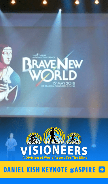 Daniel Kish Keynote at Aspire. IMage: Photo of Daniel Kish on stage beneath a video screen with the logo of Brave New World , the theme of the 2018 Aspire global conference in Krakow, Poland.