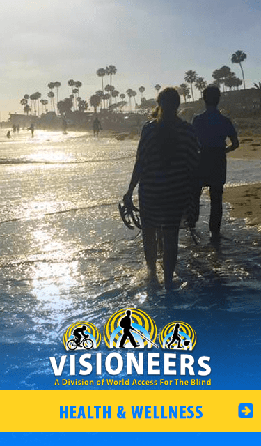 Health and Wellness Visioneering: Image: Daniel Kish is shown walking with a young woman along the water at Corona Del Mar beach in the late afternoon sun.