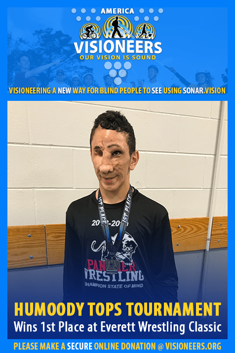 Visioneers Facebook Module frames a photo of Humoody Smith with a gold medal hanging around his neck after winning first place in his division at the Everett Classic Wrestling Tournament in Everett, Washington. Text: Humoody Tops Tournament. Wins 1st Place at Everett Wrestling Classic.