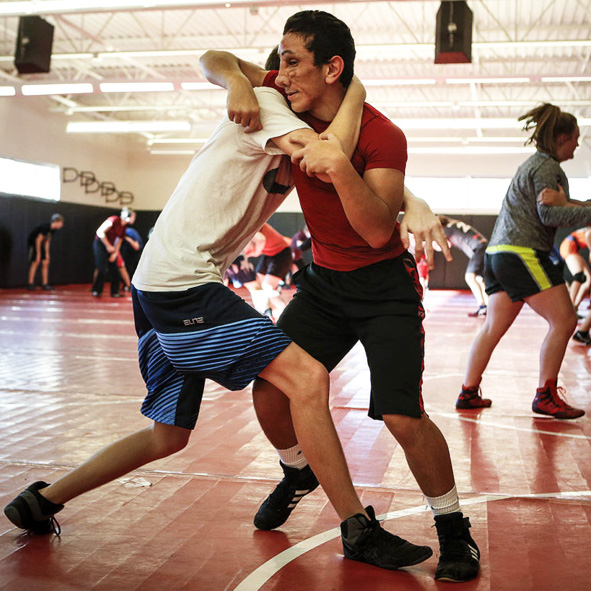 Image: Humoody Smith - in the red t-shirt - wrestles with teammate Paul Johnson during a practice at his high school.