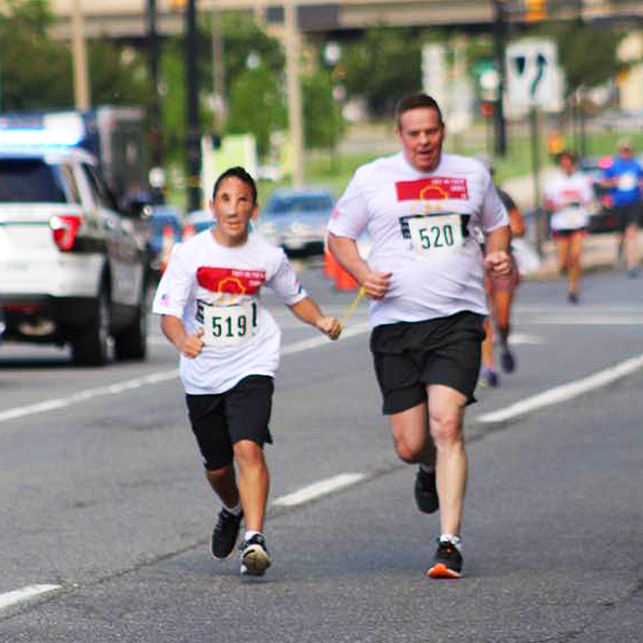 Humoody and his dad Randy Smith run side by side joined by a tether during the 5k fundraising run for the Iraqi Children Foundation in Alexandria, Virginia in May 2017.