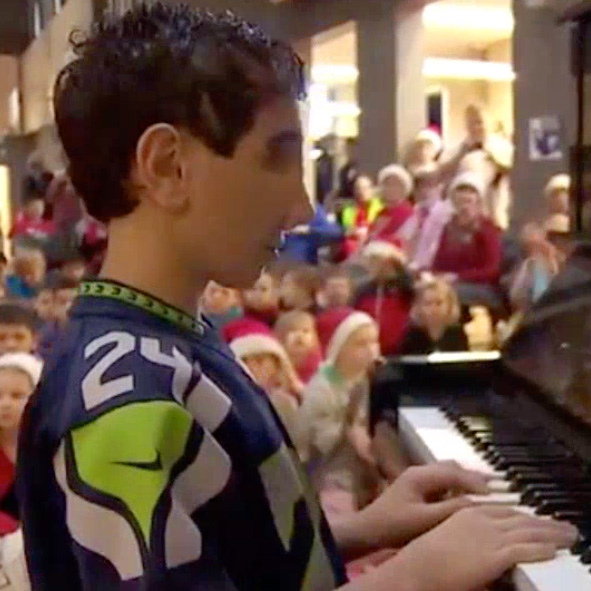 Image: Video still frame shows Humoody wearing his Seahawks jersey while playing Christmas Carols at his school with other students in the background.