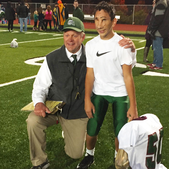 Photo shows Centennial Middle School Football Coach John Brandvold kneeling on the game field with Humoody Smith.