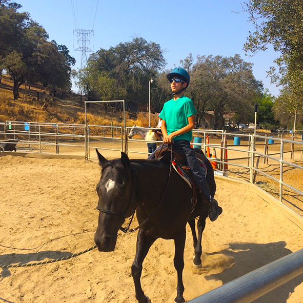 Image: Photo of Student Visioneer Nava on a therapy horse riding in a circular corral.