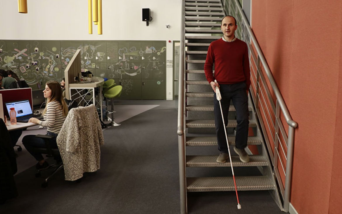 Blind entrepreneur Kursat Ceylon navigates down stairs in an office using the WeWALK smart cane he has developed.