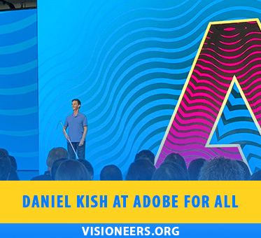 Founder and Lead Visioneer Daniel Kish presents a Keynote speech onstage at the 2019 Adobe For All Conferencenext to a stylized giant A.
