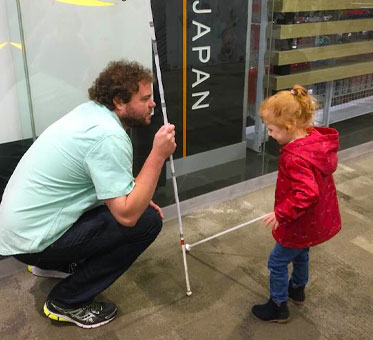 Senior Instructor Visioneer crouches down to work with a young Student Visioneer at a mall in Australia.