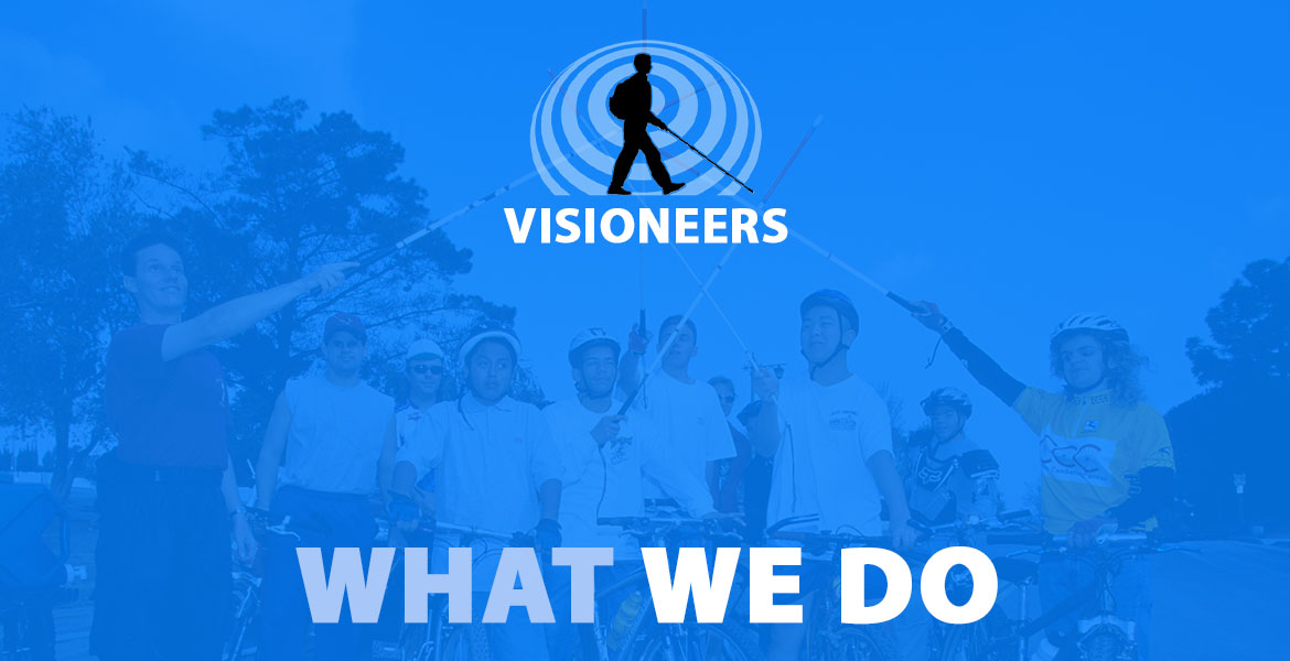 "Visioneers: What We Do. Image: Photo of Daniel Kish, Brian Bushway, Juan Ruiz and blind students stand with their bicycles and raise their perceptual navigation canes in an ""all for one and one for all"" salute."