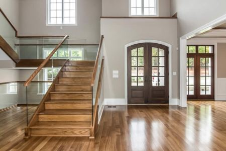 Staircase with Glass panel handrail and Wood Front Entry Door