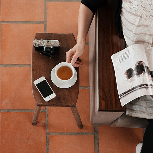 woman sitting with coffee reading a magazine