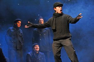A man dressed in a black sweater, black pants, black scarf and black hat is singing in the forefront with his arms wide open, and similarly dressed men are standing and listening in the background.