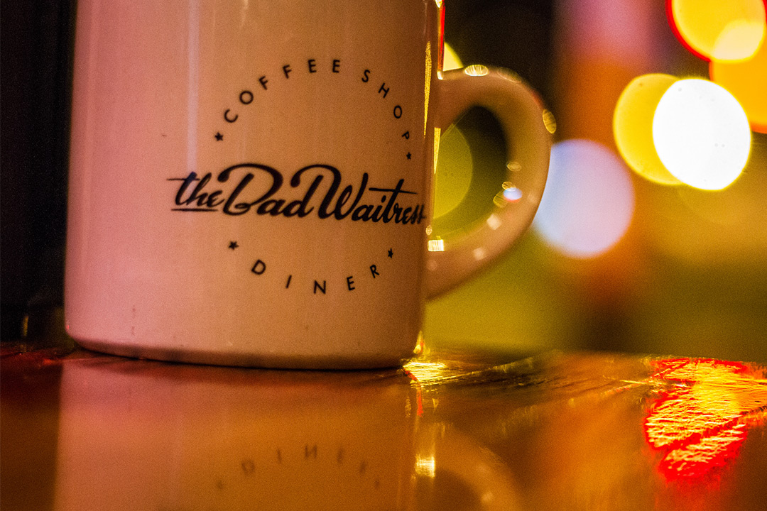 The Bad Waitress Coffee Mug on a table in Minneapolis