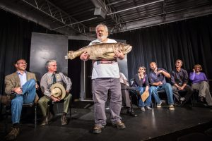A group of people are sitting in a line horizontally behind a man who is standing and holding a large fish with two hands.