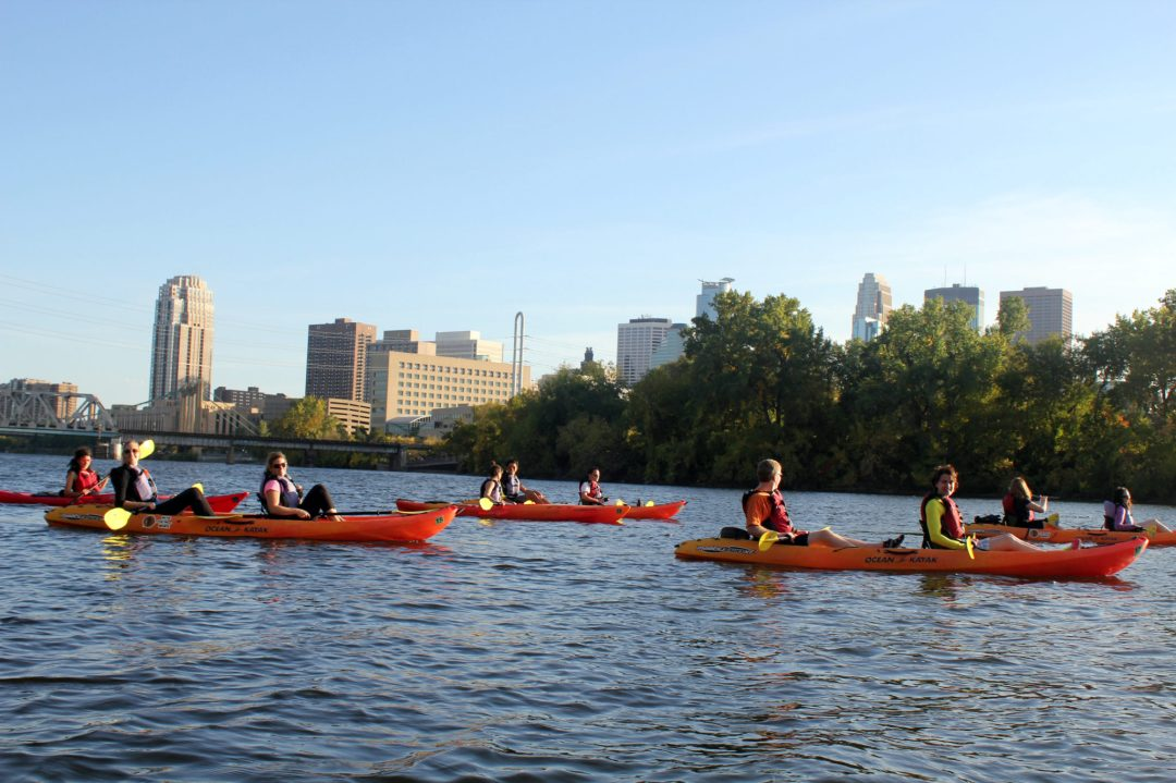 A group of kayakers out for a morning stroll on the Mississippi River. In the background is the Minneapolis skyline.
