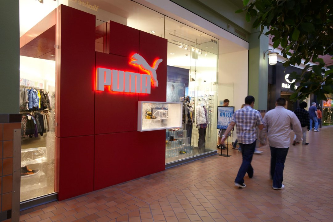 Two men walking past the Puma storefront. Their sign is made up of red blocks with the white Puma logo placed across them.