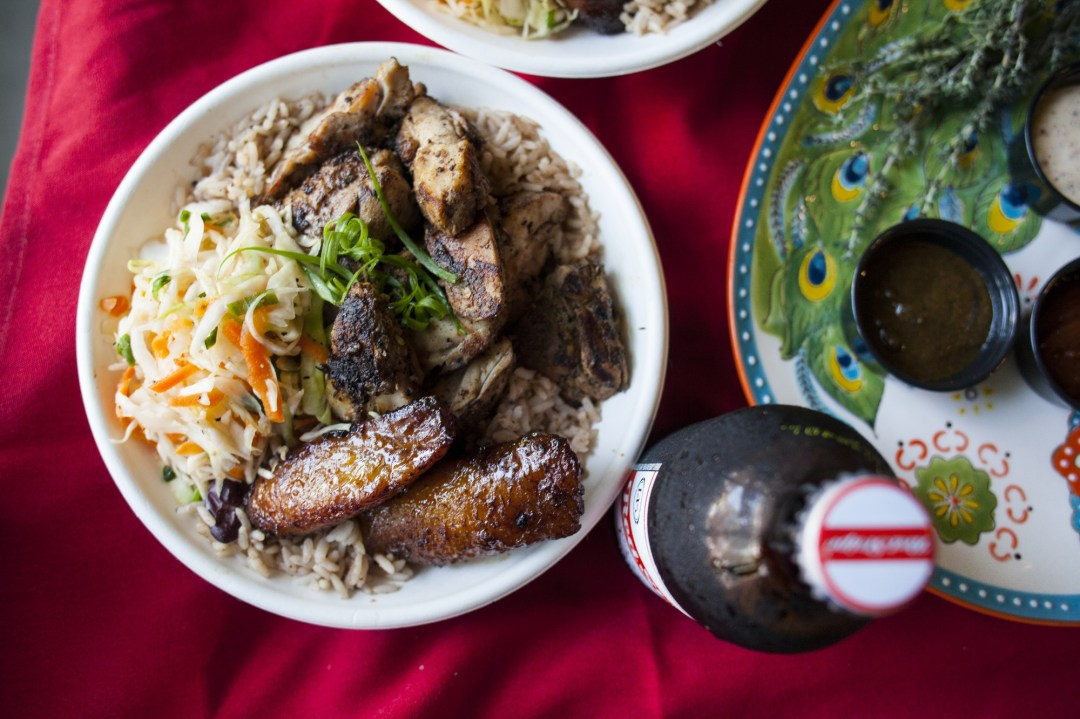 Jerk chicken, marinated in our signature jerk rub, then fire-grilled, on a plate next to a bottle of Red Stripe beer.
