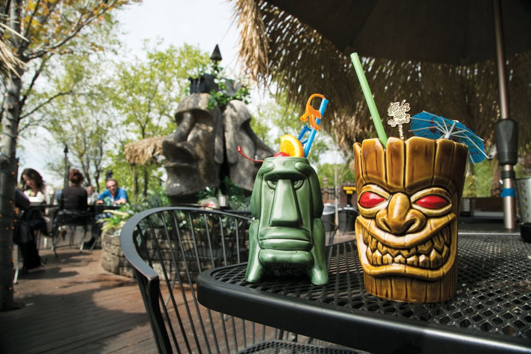 Two tiki-inspired mugs are sitting on a table on Psycho Suzi's patio. Easter Island-inspired heads are sitting in the background.