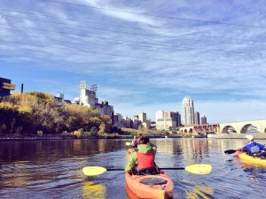 A view of the skyline and kayakers on the river.