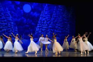 Ballerinas dance around a couple in the middle on stage. The backdrop is a winter night.