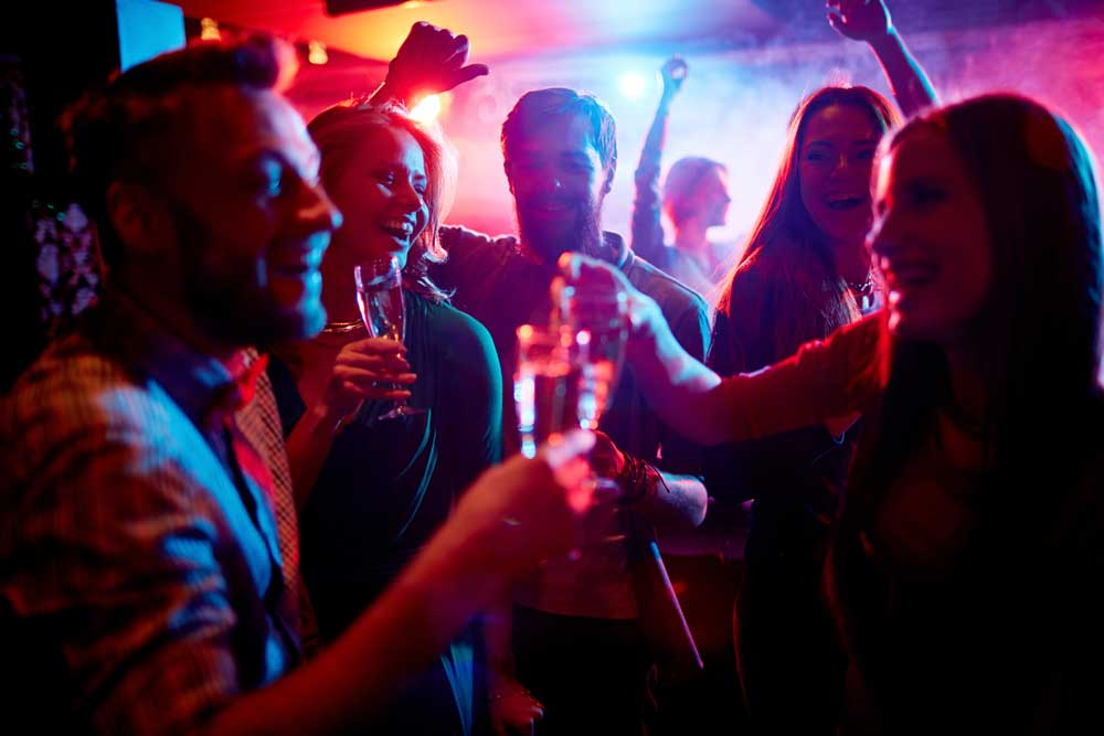 People dancing and toasting drinks at a nightclub. The Metro Transit Blue Line will drop you off downtown Minneapolis, one of the best locations for nightlife in the Twin Cities.
