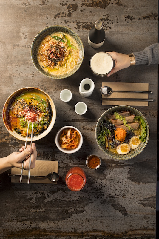 Birds eye view of ramen dishes on a table with two beers and hands reaching in for food.