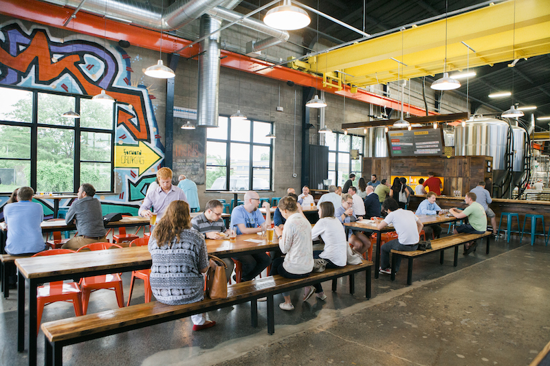 People sitting at picnic table style seating inside a colorful brewery drinking beer.