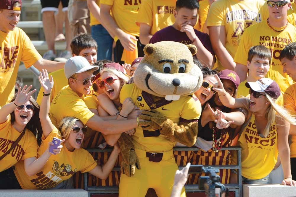 Students posing for a photo with Goldy Gopher at a University of Minnesota football game. Just one of the many stops along the Metro Transit Green Line.