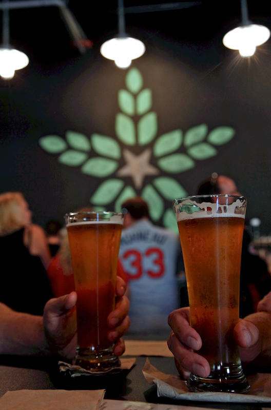Two glasses full of beer in front of a brewery logo and man wearing a baseball jersey