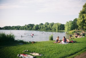 People enjoy the sun and the water on the shore of Lake Nokomis Park.