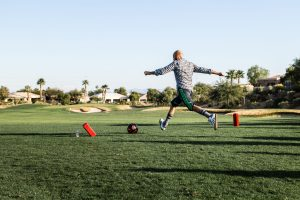 A man kicks a soccer ball on a golf course while playing FootGolf.