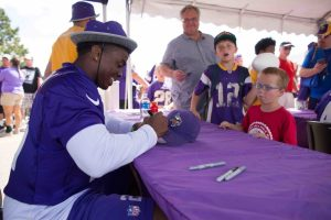 Vikings player signs a hat for a young fan.