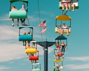 People sitting in colorful seats, riding above a fair. Free summer events in the Twin Cities