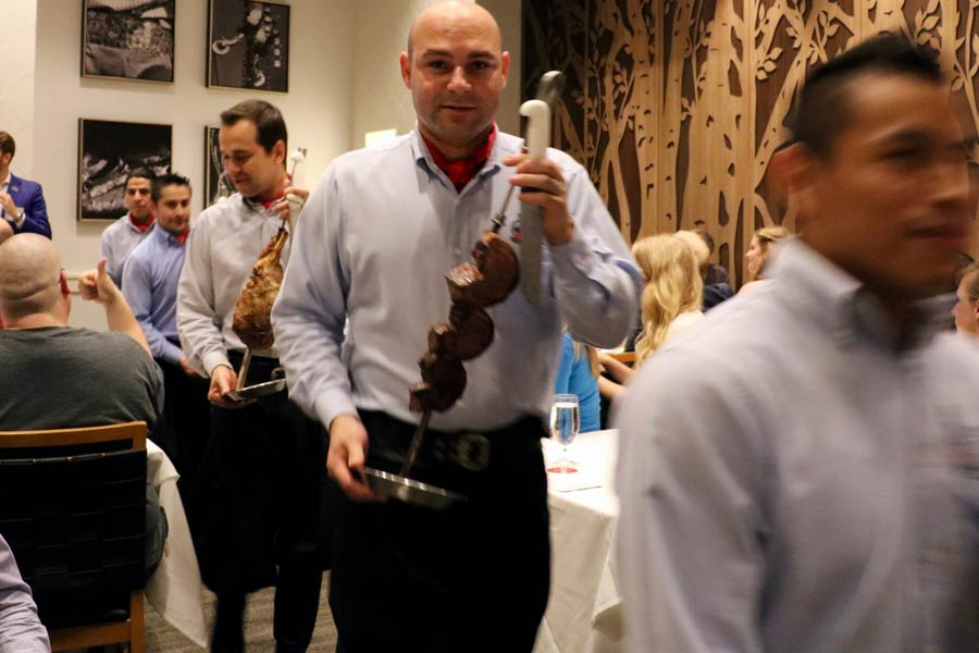 Server at Fogo de Chao carrying meat at preview day