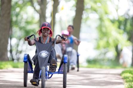 Woman rides Wheel Fun Rentals bike around a park.