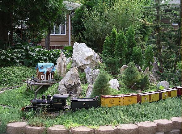A train winds its way around a rock garden in the Lutz Railroad Garden.