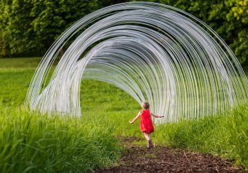 Photo of little girl running through metal arcs of a tree house at the Minnesota Landscape Arboretum's tree houses exhibit.
