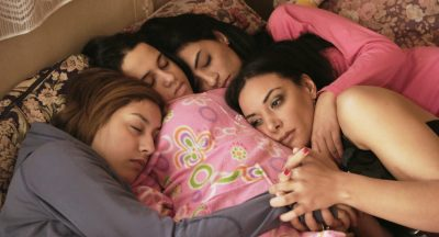 A still from Much Loved shows the four women embracing, lying on a bed together.