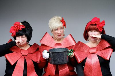 Photo by Tammy Brice, courtesy of Plymouth Playhouse. Three of the Looney performers holding a stinking pot of lutefisk and holding their noses. (They're also adorned in huge holiday bows.)