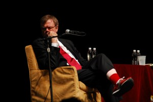 Photo of Garrison Keillor on stage sitting in an armchair in front of a microphone
